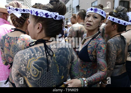 TOKYO, JAPAN - MAY 18: Heavily tattooed Japanese women stand in the street as they wait for the portable shrine in the street of Asakusa during 'Sanja Matsuri' on May 18, 2019 in Tokyo, Japan. A boisterous traditional mikoshi (portable shrine) is carried in the streets of Asakusa to bring goodluck, blessings and prosperity to the area and its inhabitants. (Photo: Richard Atrero de Guzman/ AFLO) - Stock Photo