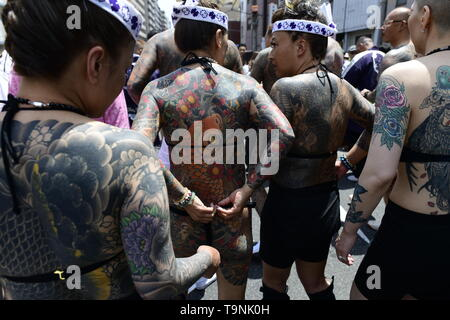 TOKYO, JAPAN - MAY 18: Heavily tattooed Japanese women chat in the street as they wait for the portable shrine in the street of Asakusa during 'Sanja Matsuri' on May 18, 2019 in Tokyo, Japan. A boisterous traditional mikoshi (portable shrine) is carried in the streets of Asakusa to bring goodluck, blessings and prosperity to the area and its inhabitants. (Photo: Richard Atrero de Guzman/ AFLO) - Stock Photo