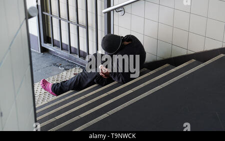 Berlin, Germany. 18th May, 2019. A homeless guy sits on stairs at a suburban train entrance. Credit: Annette Riedl/dpa/Alamy Live News - Stock Photo