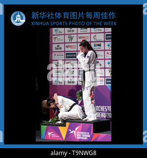 (190520) -- BEIJING, May 20, 2019 (Xinhua) -- XINHUA SPORTS PHOTO OF THE WEEK (from May 13 to May 19, 2019) TRANSMITTED on May 20, 2019. China's Zheng Shuyin cries as she collapses on the podium after being controversially beaten by Great Britain's Bianca Walkden (R) after the women's  73kg final at the World Taekwondo Championships 2019 in Manchester, Britain on May 17, 2019. (Xinhua/Jon Super) - Stock Photo