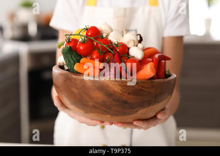 Cute little chef with vegetables in kitchen, closeup - Stock Photo