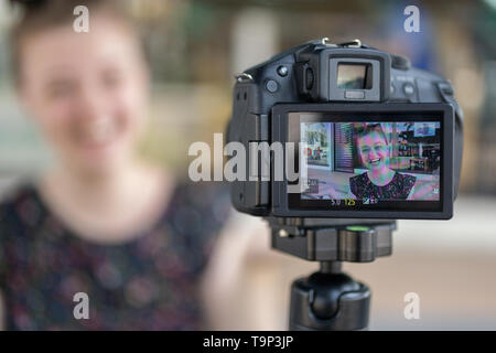 Manila, Philippines - May, 18, 2019: A caucasian young girl making a video blog (vlog) behind the camera - Stock Photo