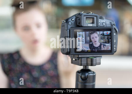 A caucasian young girl making a video blog (vlog) behind the camera - Stock Photo