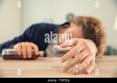 Unconscious drunk man with bottle and empty glass at table. Alcoholism concept - Stock Photo