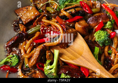 Chinese noodles with vegetables and meat in wok, closeup - Stock Photo