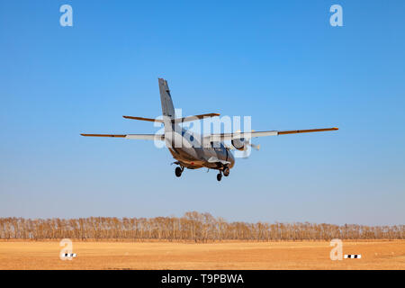 A small aircraft for the transport of passengers and paratroopers lands in a field on a landing strip with grass under a blue sky above the trees on a - Stock Photo