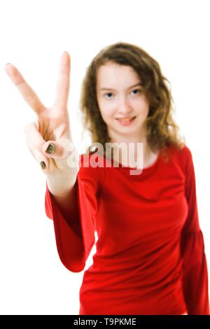 Slim girl in red dress showing victory sign with two fingers - focus on fingers, blurry face in background - Stock Photo