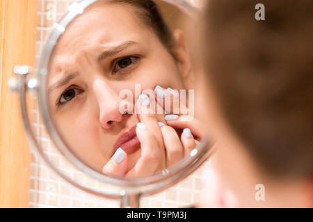 Young girl squeezes pimple on the fer face in front of a bathroom mirror. Beauty skincare and wellness morning concept. - Stock Photo
