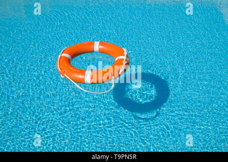 Life belt floating on water in a swimming pool creating a shadow - Stock Photo