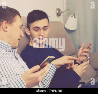 Guy with his father are resting and playing on phone at the home. - Stock Photo