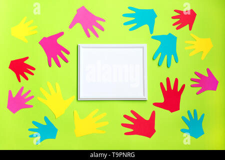 AUTISM. Cut out of colored paper children palms around white frame on light green background. World Autism Awareness Day, April Autism awareness month - Stock Photo