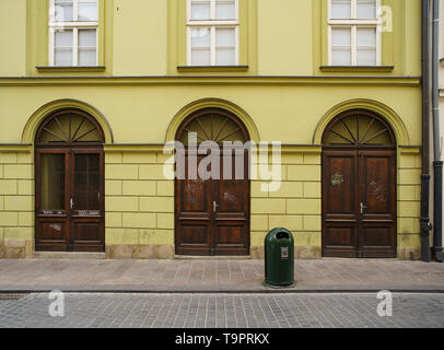 KRAKOW,POLAND-23 APRIL,2019: Three wooden doors in historic old Polish town in Europe. Beautiful European architecture in close up. Yellow stone house and dark brown doors made of wood - Stock Photo