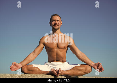 Yoga helps find balance and unite with nature. Yoga practice helps find harmony and balance. Man practicing yoga blue sky background. Reached peace of - Stock Photo