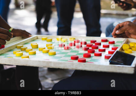 man playing chinese checkers in the streets - Stock Photo