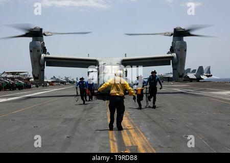 190517-N-GD018-1219 ARABIAN SEA (May 17, 2019) Sailors remove chocks and chains from an MV-22 Osprey from Marine Medium Tiltrotor Squadron (VMM) 264 on the flight deck of the Nimitz-class aircraft carrier USS Abraham Lincoln (CVN 72). The Abraham Lincoln Carrier Strike Group (ABECSG) and Kearsarge Amphibious Ready Group (KSGARG) are conducting joint operations in the U.S. 5th fleet area of operations. The ABECSG and KSGARG, with the 22nd Marine Expeditionary Unit, are prepared to respond to contingencies and to defend U.S. forces and interests in the region. (U.S. Navy photo by Mass Communicat - Stock Photo