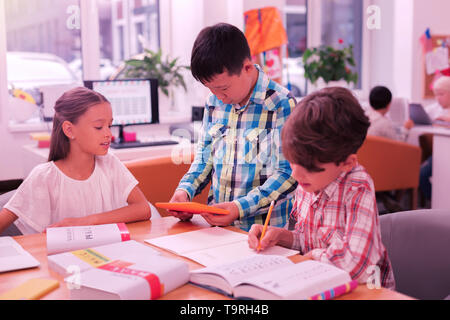 Three pupils working on their homework together. - Stock Photo
