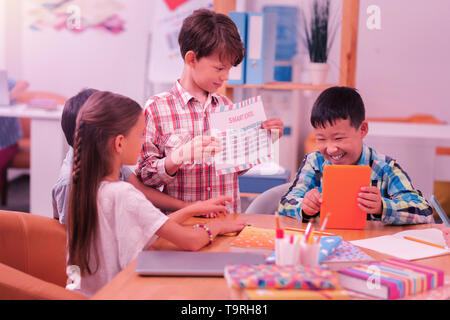 Happy schoolchildren sitting at the desk together. - Stock Photo