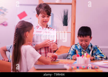 Children sitting together during the school break. - Stock Photo