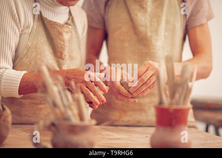 Hands of a teacher and her apprentice