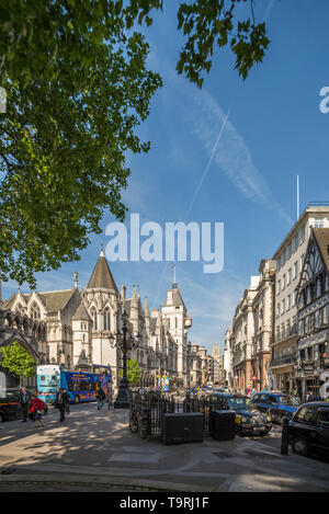 A view of Strand in Central London with The Royal Courts of Justice on the left and leafy trees hanging above on a sunny summers day - Stock Photo