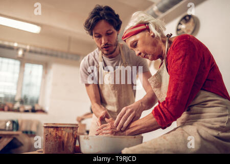 Nice pleasant man helping an aged woman