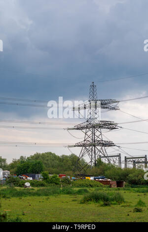 View across a field of a large electricity pylon, power lines and car scrapyard in Nursling, Test Valley, Southampton, Hampshire, southern England, UK - Stock Photo