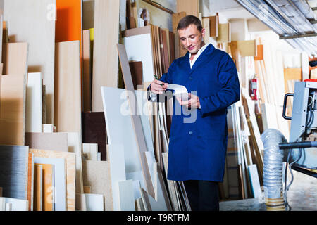 Smiling glad man wearing protective workwear standing with plywood in store - Stock Photo