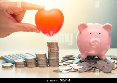 Love Heart and Saving Money Piggy Bank for Life insurance Share or Donation concept. - Stock Photo