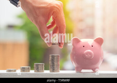 Piggy Bank With Stack of Coins,Male Hand Saving Money concept - Stock Photo