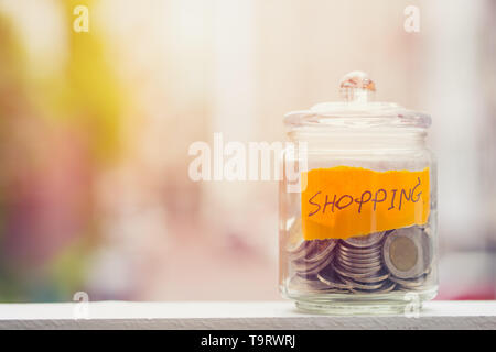 Saving money for Shopping budget, Coins keeping in glass bottle with blur background space for text - Stock Photo