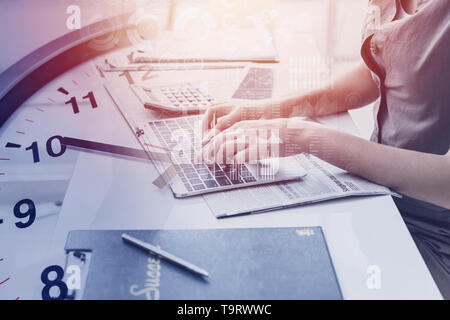 closeup hand business office woman typing on laptop computer overlay with times clock for working hours concept - Stock Photo