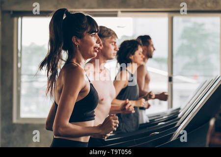 Young 20s Caucasian sporty group of men and women running together on treadmill in gym - Waist up shot - Fitness sports portrait