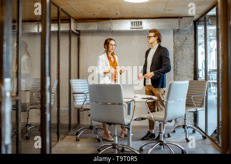 Young man and woman having a business conversation during the small conference, standing near the table in the meeting room - Stock Photo