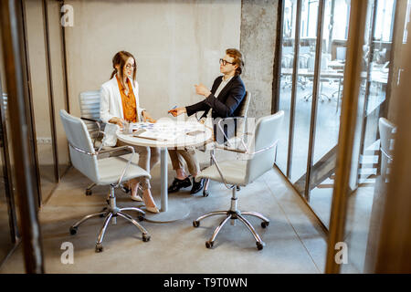 Young man and woman having a business conversation during the small conference, sitting at the round table in the meeting room - Stock Photo