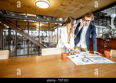 Young business man and woman working on documents at the wooden table in the office or coworking space