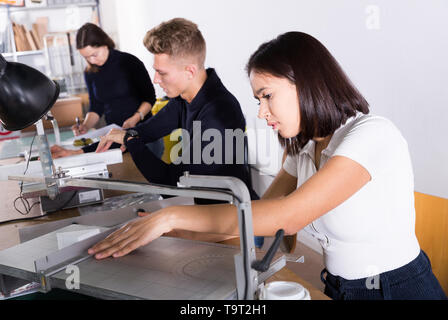Young female architect working on fret saw, creating details for new architectural model in design bureau - Stock Photo
