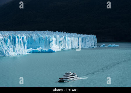 A tour boat on Lago Argentino takes tourists for a close-up view of the Perito Moreno Glacier in Los Glaciares National Park near El Calafate, Argenti - Stock Photo