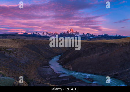 Colorful clouds in the dawn sky over Mount Fitz Roy and the Rio del las Vueltas.  Los Glaciares National Park near El Chalten, Argentina.  A UNESCO Wo - Stock Photo