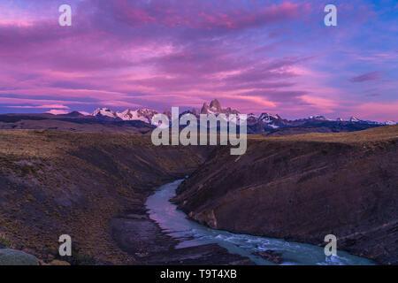 Colorful clouds in the predawn sky over Mount Fitz Roy and the Rio del las Vueltas.  Los Glaciares National Park near El Chalten, Argentina.  A UNESCO - Stock Photo