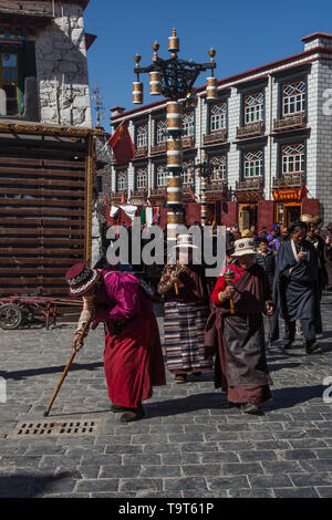 Older Tibetan women in traditional dress circumambulate the Jokhang Temple with their pray wheels in Lhasa, Tibet. - Stock Photo