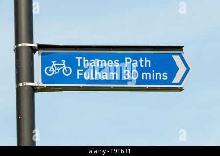 A sign marks a cycle route along the Thames Path from Hammersmith to Fulham. - Stock Photo
