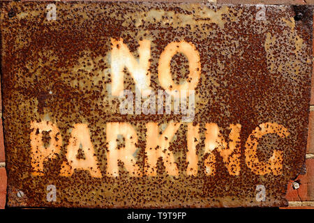 old rusty metal no parking sign on wall - Stock Photo