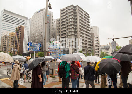 People are waiting for the green light on Harumi-dori Ave. in modern part of Tokyo, Japan. - Stock Photo