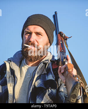 Hunter with rifle gun close up. Guy bearded hunter spend leisure hunting and smoking. Hunting masculine hobby concept. Man brutal bearded guy gamekeep - Stock Photo