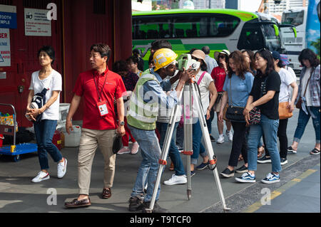 29.03.2019, Singapore, Republic of Singapore, Asia - A surveyor is taking readings from a theodolite as a group of tourists is passing by. - Stock Photo