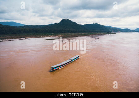 View from above. Stunning aerial view of a traditional long-tail boat sailing on the Mekong river, Luang Prabang, Laos. top view, aerial view - Stock Photo