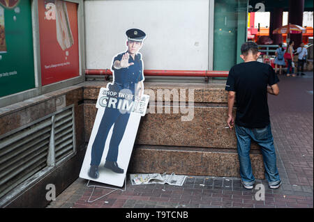 29.03.2019, Singapore, Republic of Singapore, Asia - A man is smoking a cigarette next to a cardboard put-up hinge in Chinatown. - Stock Photo