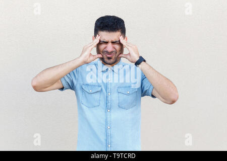 headache, confusion or problem. Portrait of sick handsome young bearded man in blue shirt standing and holding his head and feeling bad. indoor studio - Stock Photo