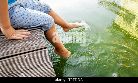 Closeup image of child sitting on the wooden pier at tiver and holding feet in water. Kids playing and splashing water with legs - Stock Photo