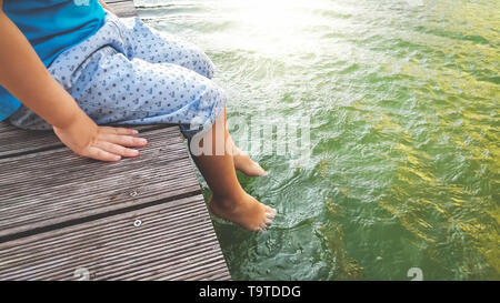 Closeup photo of 3 years old little boy sitting on the wooden pier and holding his feet in river water. CHild splashing in lake with legs - Stock Photo